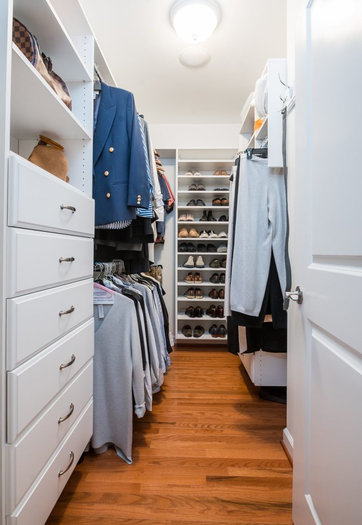Wall-in closet with white cabinetry and medium hardwood flooring (different angle)