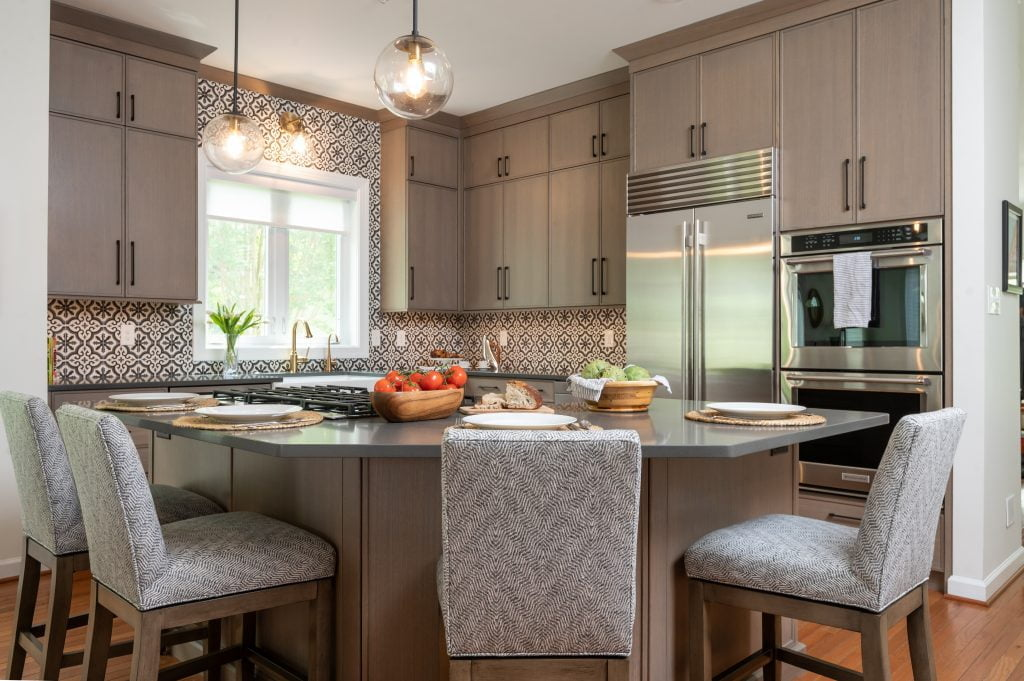 Kitchen island with light brown cabinetry, matching hi-top chairs, and dark countertops (whole kitchen) (different angle)