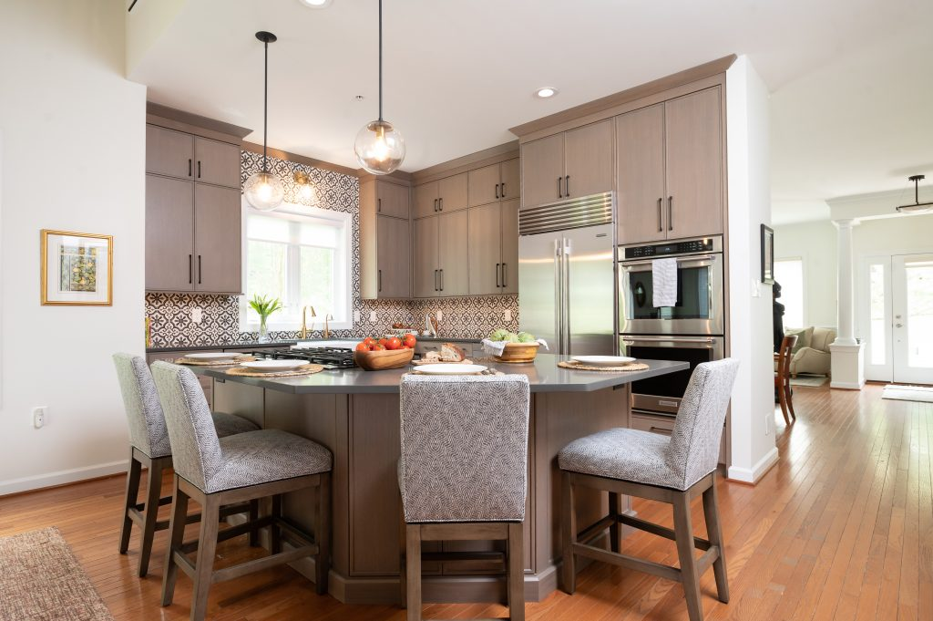 Kitchen island with light brown cabinetry, matching hi-top chairs, and dark countertops (whole kitchen) (different angle) (2)
