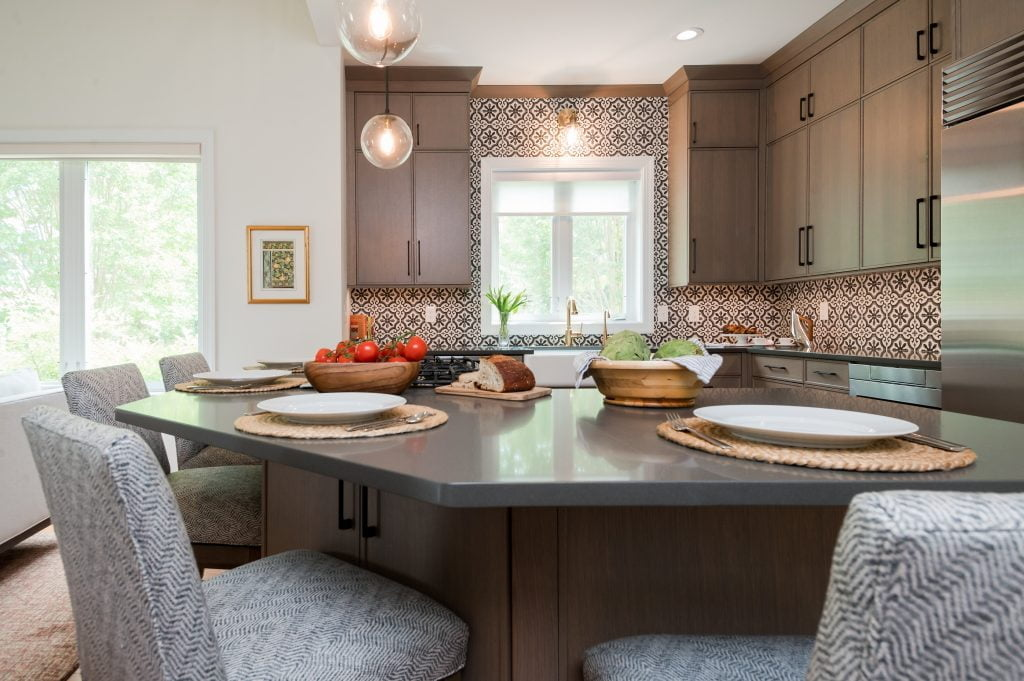 Kitchen island with light brown cabinetry, matching hi-top chairs, and dark countertops (whole kitchen) (zoomed out)