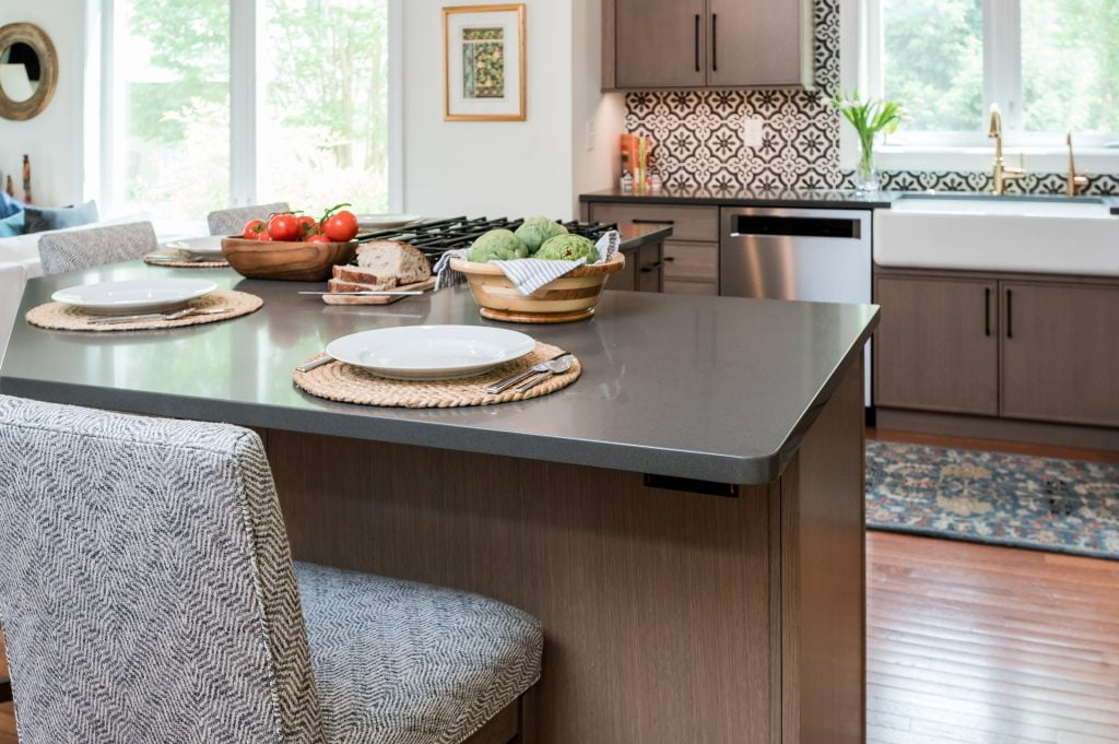 Kitchen island with light brown cabinetry, matching hi-top chairs, and dark countertops (zoomed out)