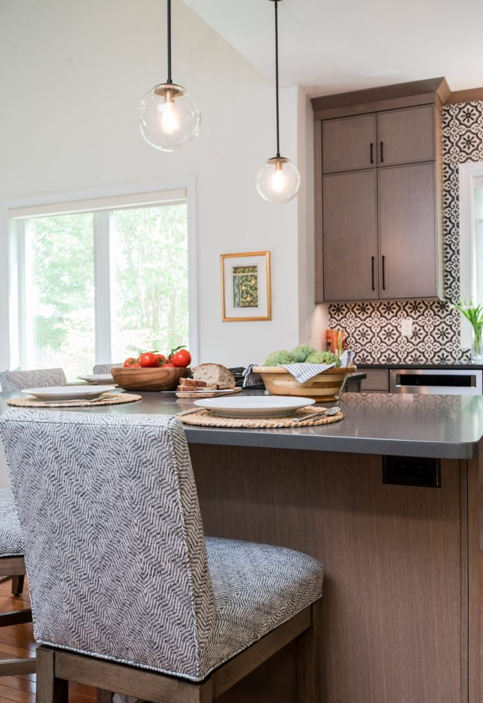 Kitchen island with light brown cabinetry, matching hi-top chairs, and dark countertops