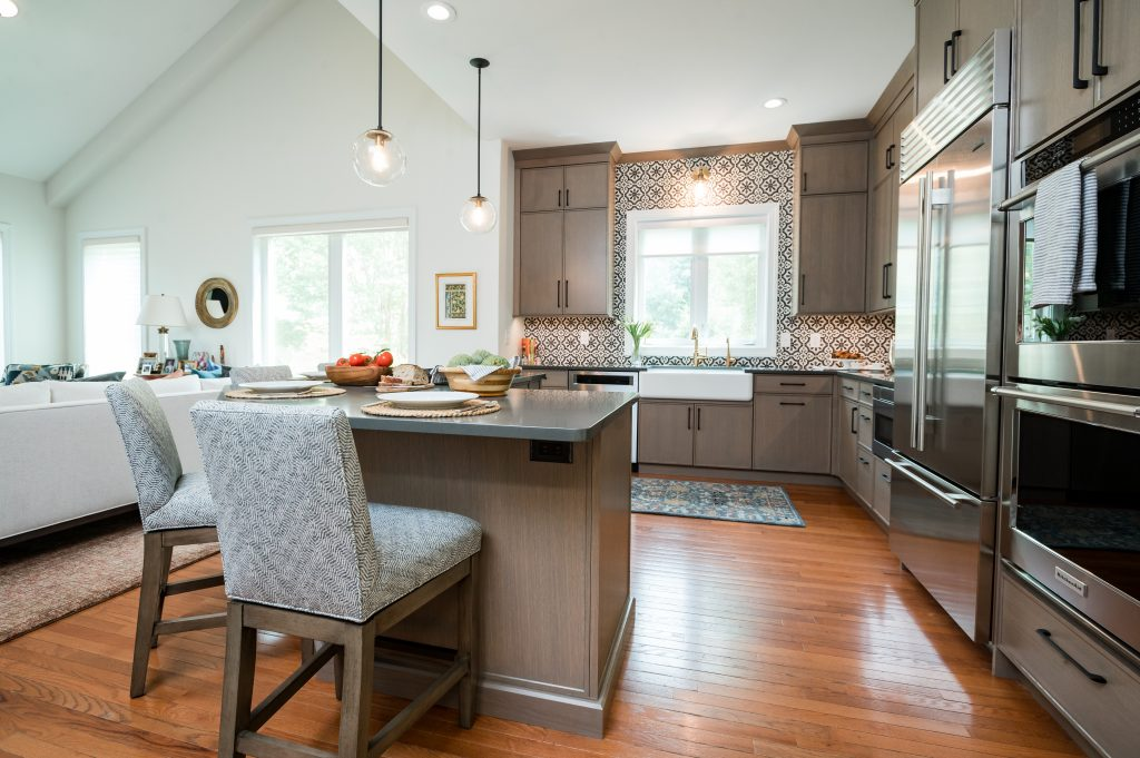 Patterned tile backsplash and custom white and gold sink and faucet with light brown cabinetry (whole kitchen) (zoomed out)
