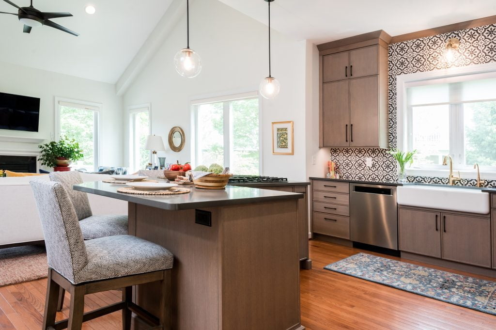 Patterned tile backsplash and custom white and gold sink and faucet with light brown cabinetry (whole kitchen)