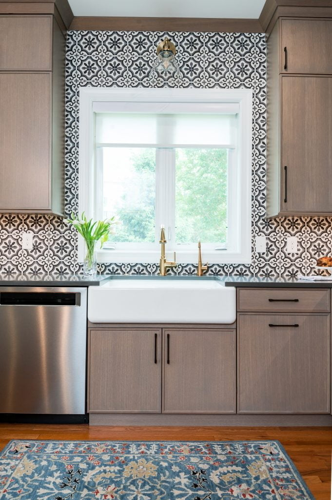 Patterned tile backsplash and custom white and gold sink and faucet