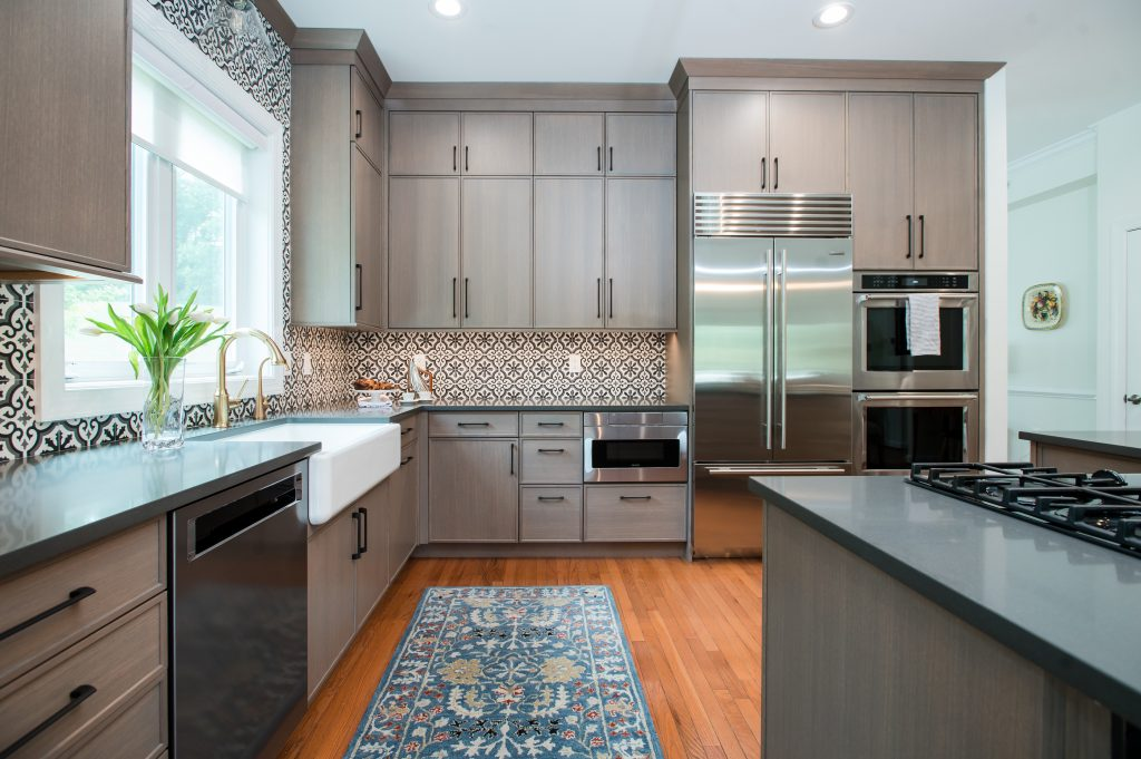 Transitional kitchen with light brown cabinetry, medium hardwood flooring, stainless steel appliances, and patterned tile backsplash