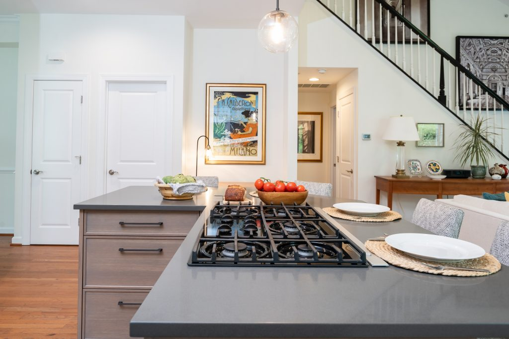Gas stovetop on kitchen island with dark countertops and light brown cabinetry