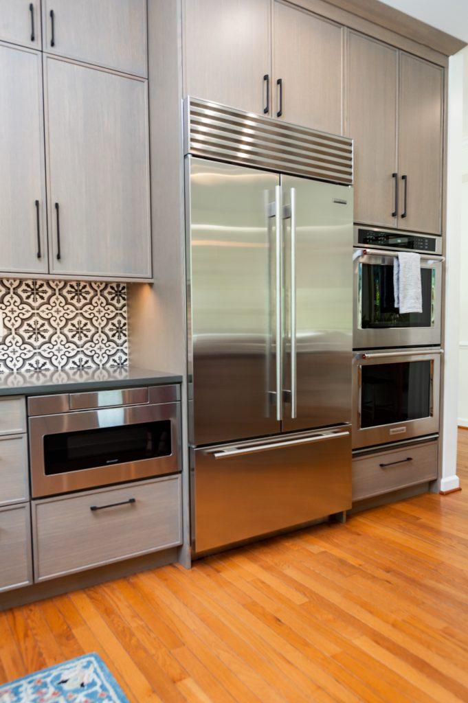 Transitional stainless steel refrigerator on medium hardwood flooring around grey cabinetry