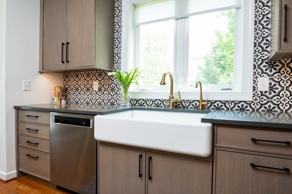 View of tinted gold faucet, full sink, and backsplash in transitional kitchen (Zoomed out)