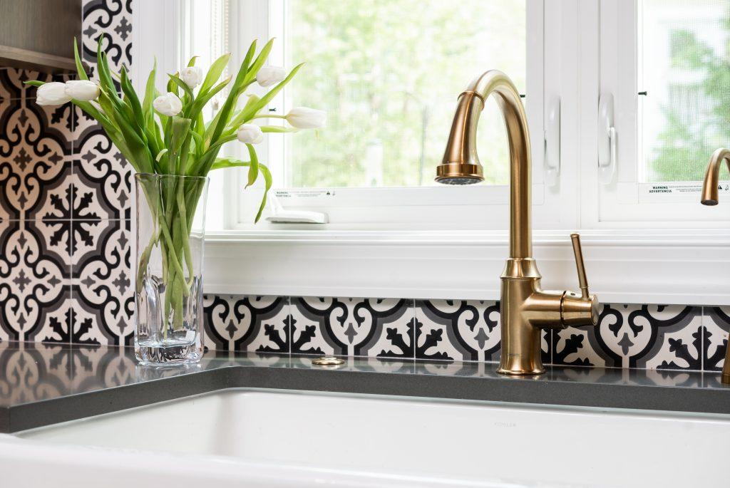 View of tinted gold faucView of tinted gold faucet, sink, and backsplash in transitional kitchenet, sink, and backsplash