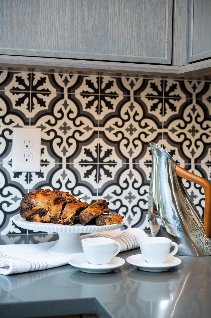 Decorative corner of food and drink on a dark countertop and patterned tile backsplash