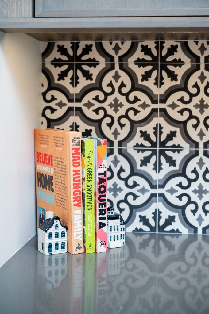Decorative corner of books on a dark countertop and patterned tile backsplash