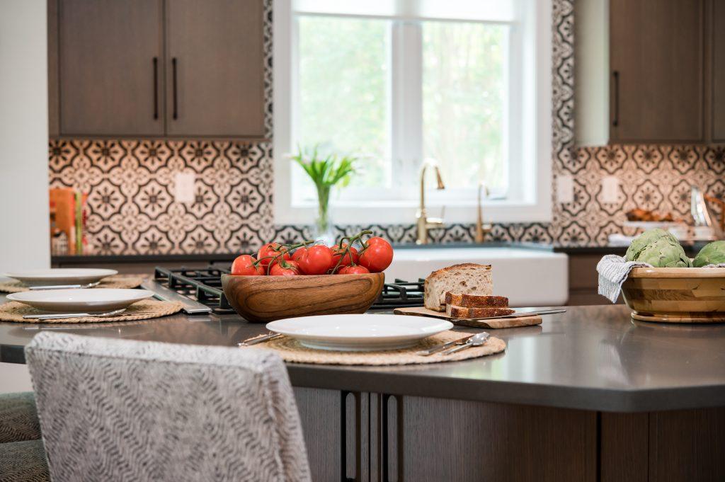 High end dark countertop with patterned tile backsplash and dark cabinetry kitchen