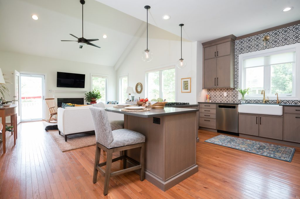 Bright kitchen with dark beige white oak cabinetry, dark countertops, and patterned black, white and grey tile backsplash; view into living room