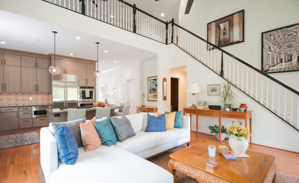 Bright and airy open plan living room and kitchen. Black banister on staircase.
