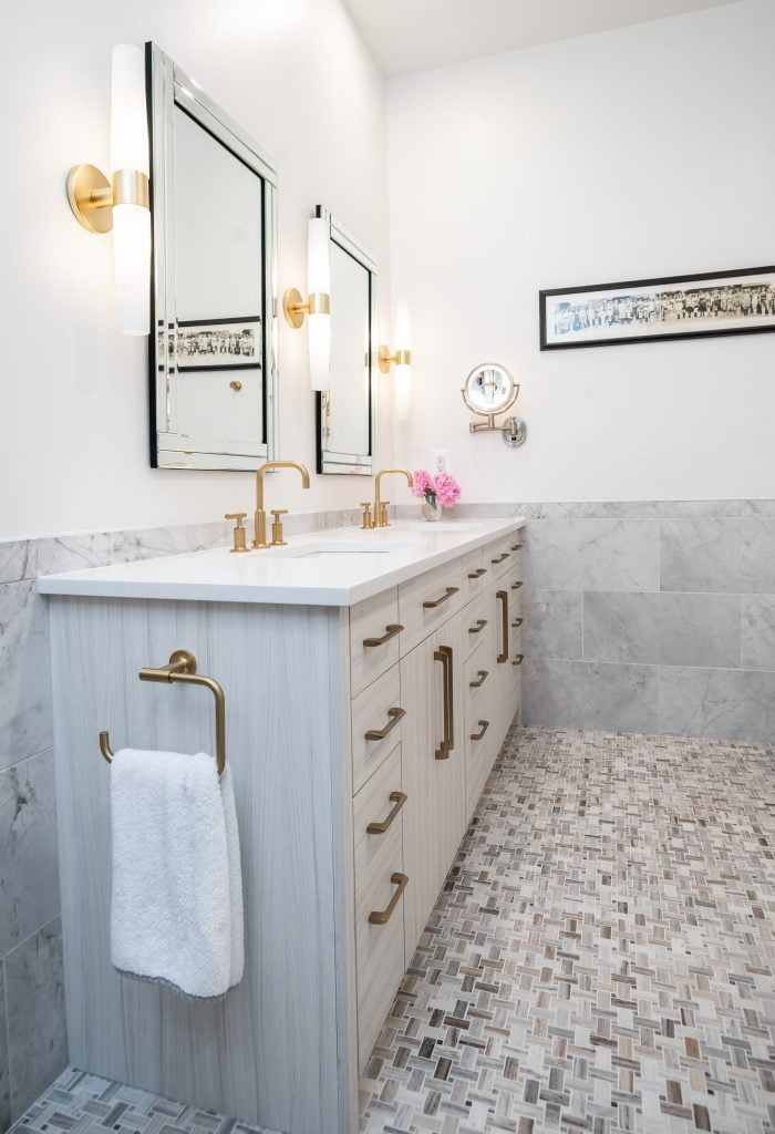White, grey and gold bathroom with double vanity and gold accents.