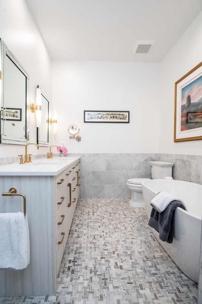 White, grey and gold bathroom with large white free standing soaking tub, double vanity and toilet with gold accents.