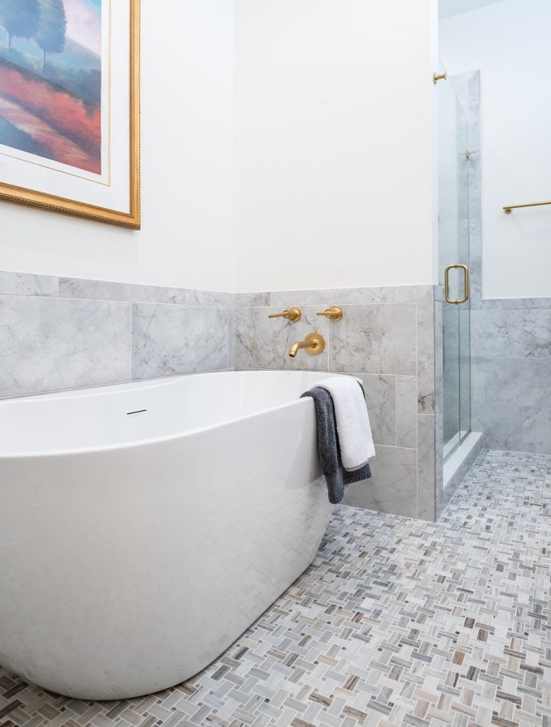White and grey marble wainscoting with large white free standing soaking tub with gold accents. Glass and marble shower.