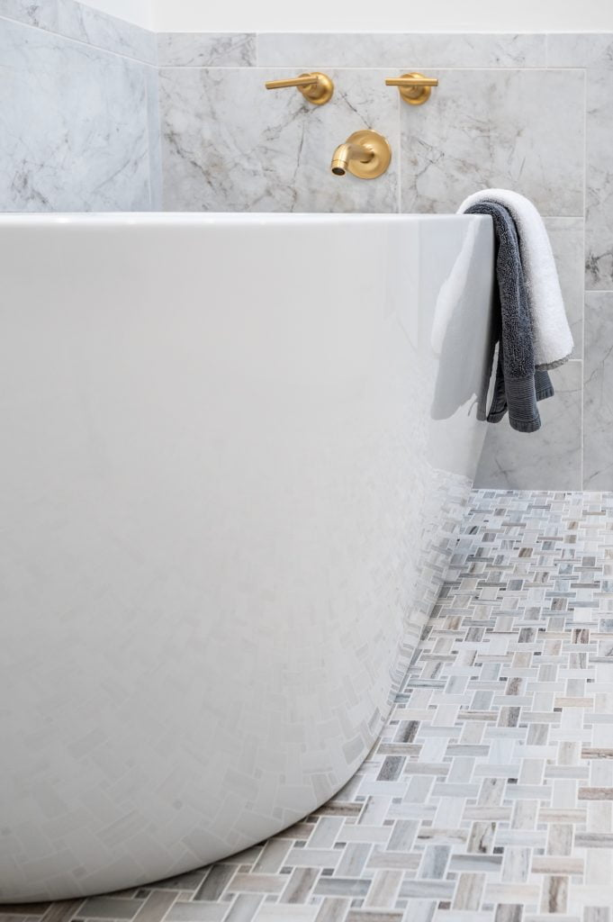 White and grey marble wainscoting with large white free standing soaking tub with gold accents.