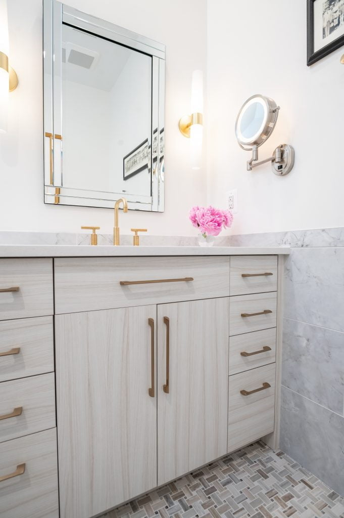 White and grey marble wainscoting with bathroom vanity, gold accessories and a large mirror.