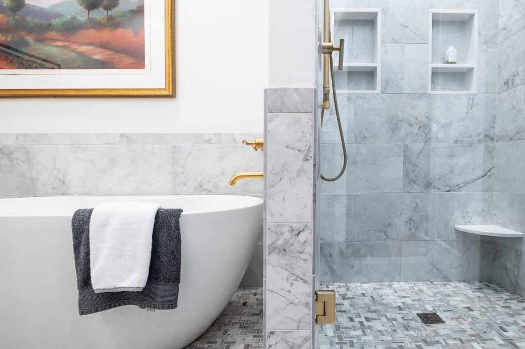 White free standing soaking tub next to a grey and white marble shower with gold accents