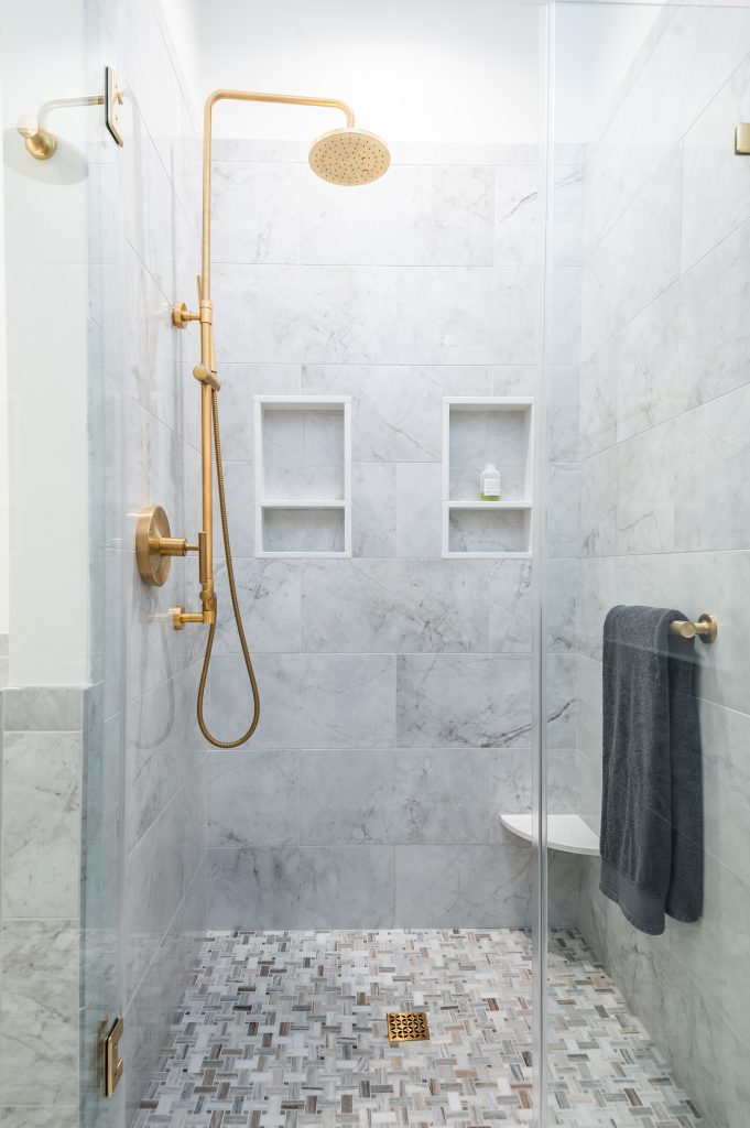 View of gold-plated shower faucet inside a marble shower