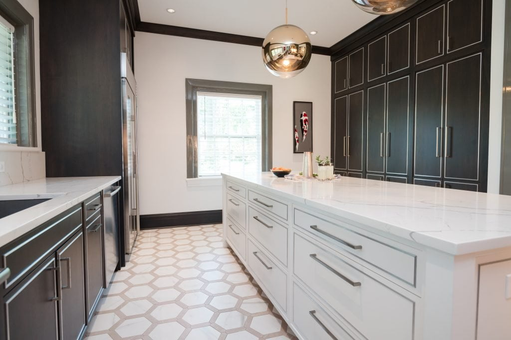 Modern/high end kitchen and island with all marble countertops, custom dark cabinetry and custom white cabinetry on island, and decorative hexagonal tile flooring