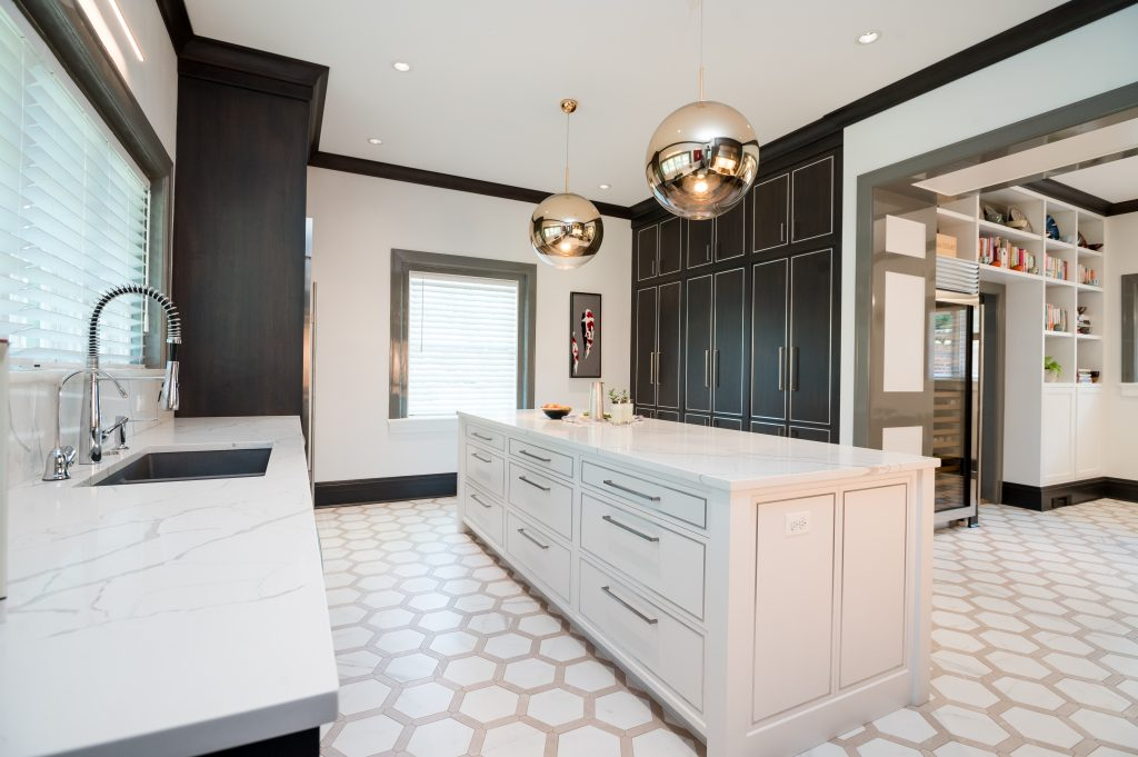 Modern/high end kitchen and island with all marble countertops, custom dark cabinetry and custom white cabinetry on island, and decorative hexagonal tile flooring (Zoomed out)