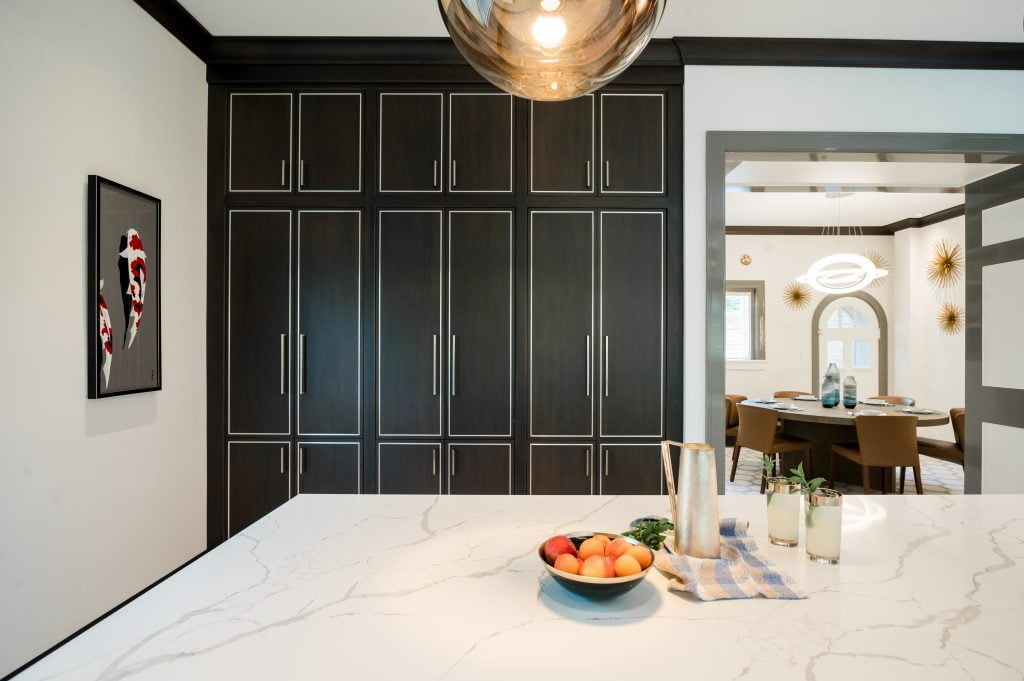 Custom floor-to-ceiling dark wood cabinetry in modern kitchen