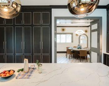 Custom floor-to-ceiling dark cabinetry from behind marble island countertop