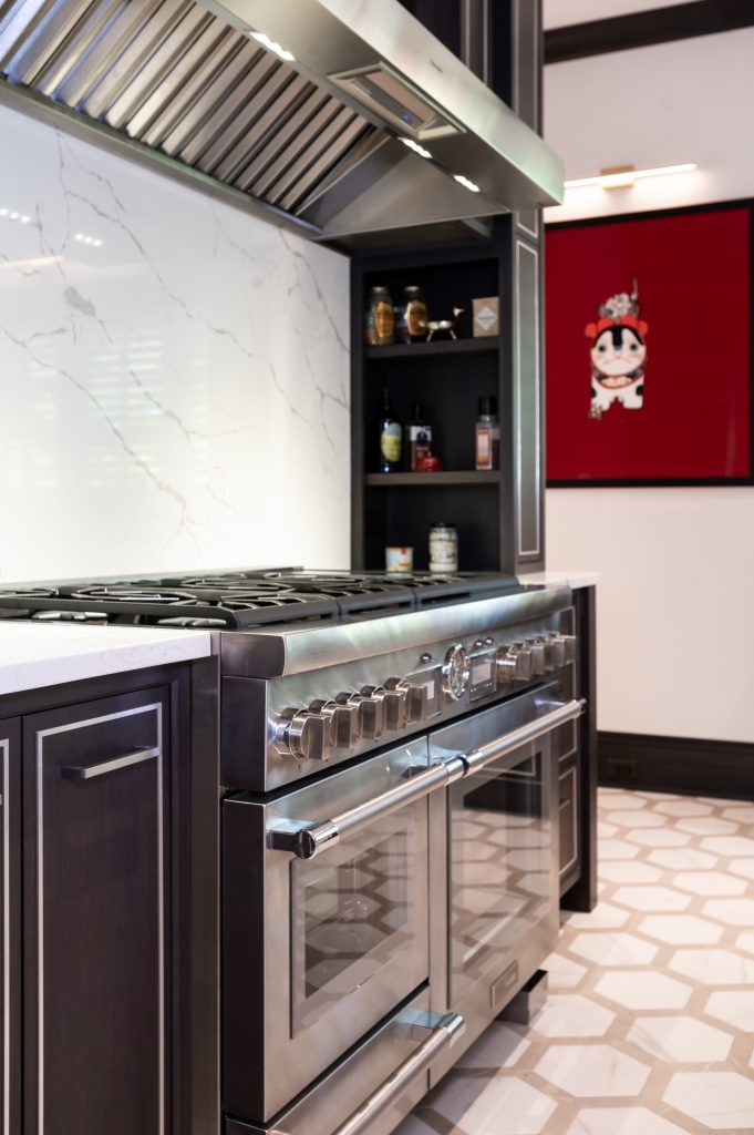 Modern appliance counter with stainless steel ovens and hood vent (zoomed in)