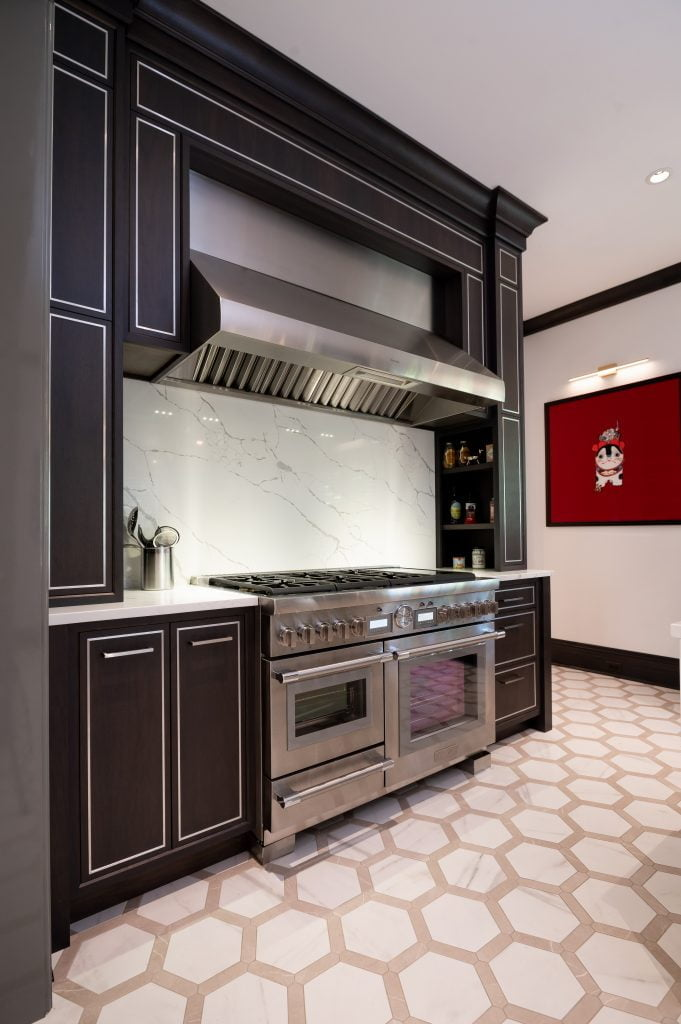 Modern kitchen counter with floor-to-ceiling custom dark wood cabinetry, stainless steel ovens and hood vent, and hexagonal tile flooring