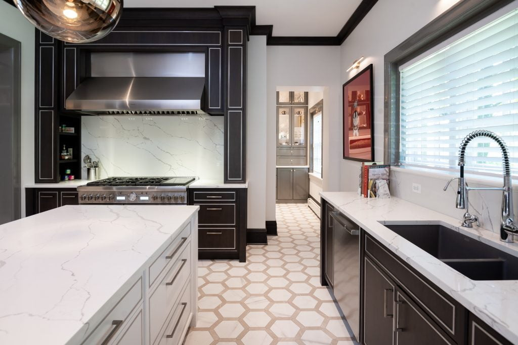Modern/high end kitchen and island with all marble countertops, custom dark cabinetry and custom white cabinetry on island, and decorative hexagonal tile flooring (different view)