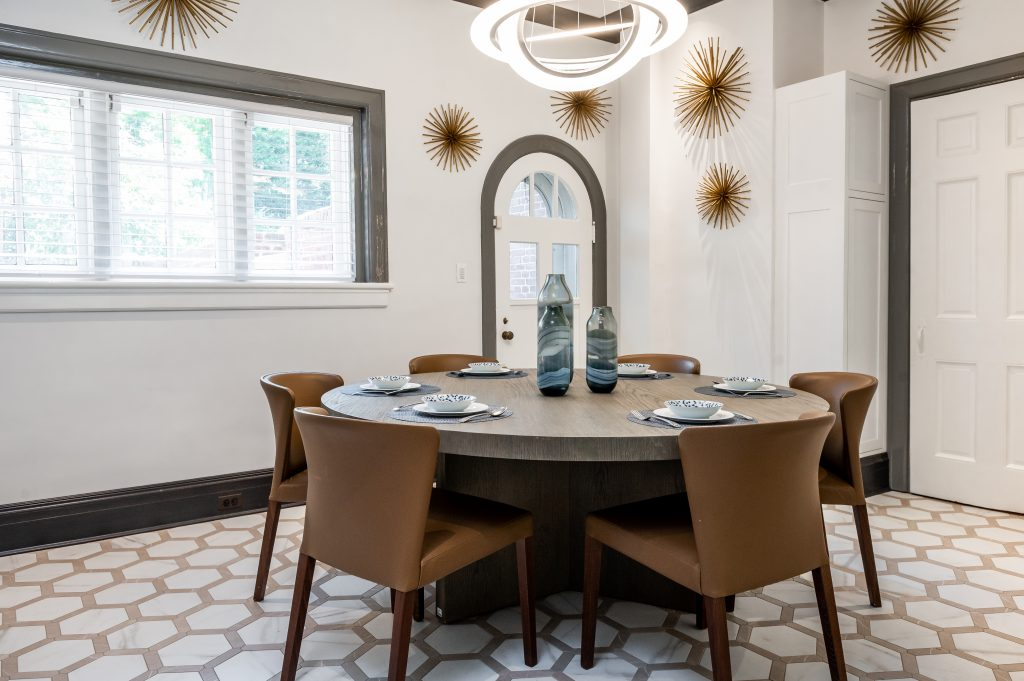 High end dining room with dark wood table, leather chairs and hexagonal tile flooring