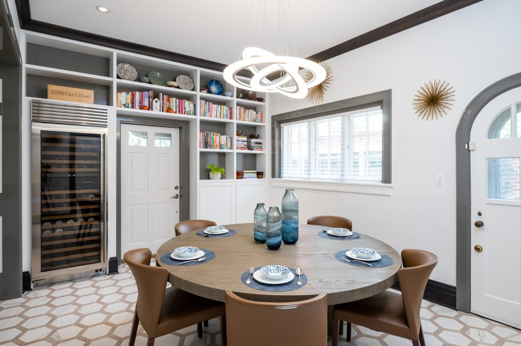 Contemporary dining room with wood table, leather chairs. decorative overhead light, and large wine cooler