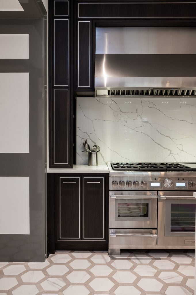 High end kitchen with dark cabinetry, stainless steel appliances, and marble countertops and backsplash