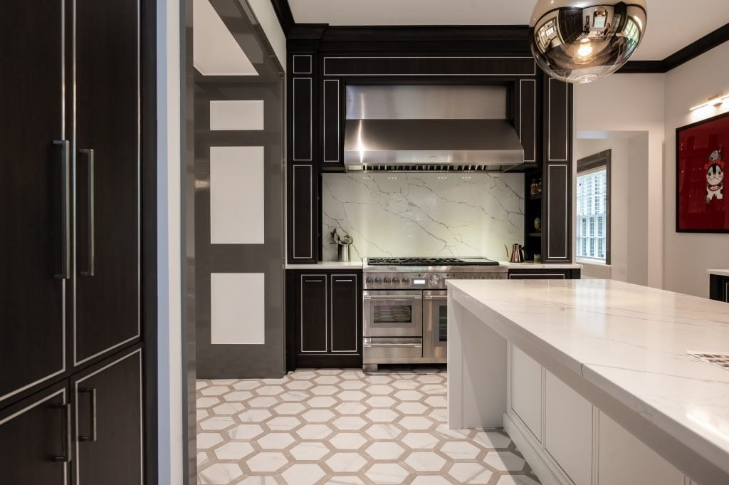 Modern/high end kitchen and island with all marble countertops, custom dark cabinetry and custom white cabinetry on island, and decorative hexagonal tile flooring (left view)