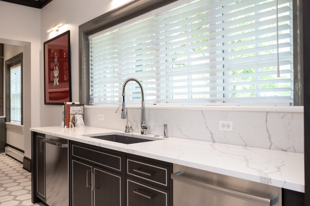 Marble countertops in high end kitchen space with stainless steel faucet
