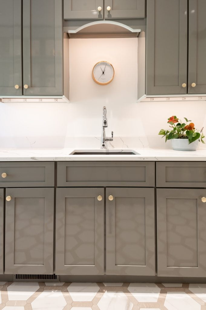 Transitional kitchenette with grey cabinetry, marble countertops, and hexagonal tile flooring (front view)