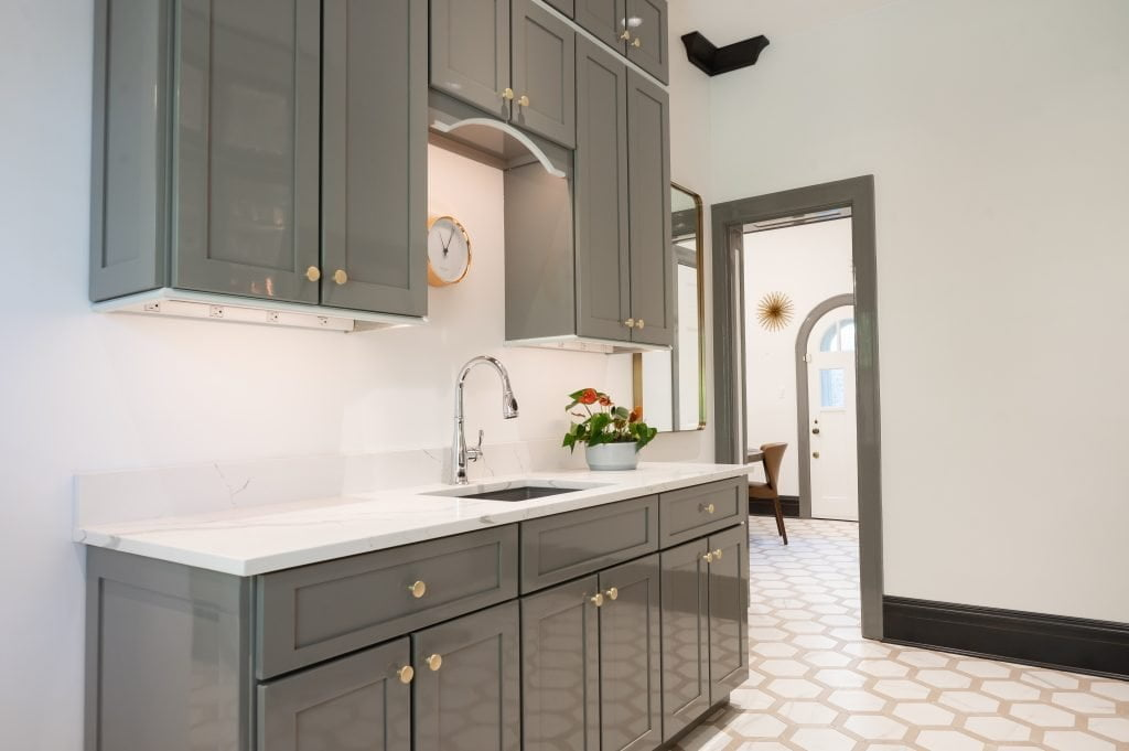 Transitional kitchenette with grey cabinetry, marble countertops, and hexagonal tile flooring (different view)