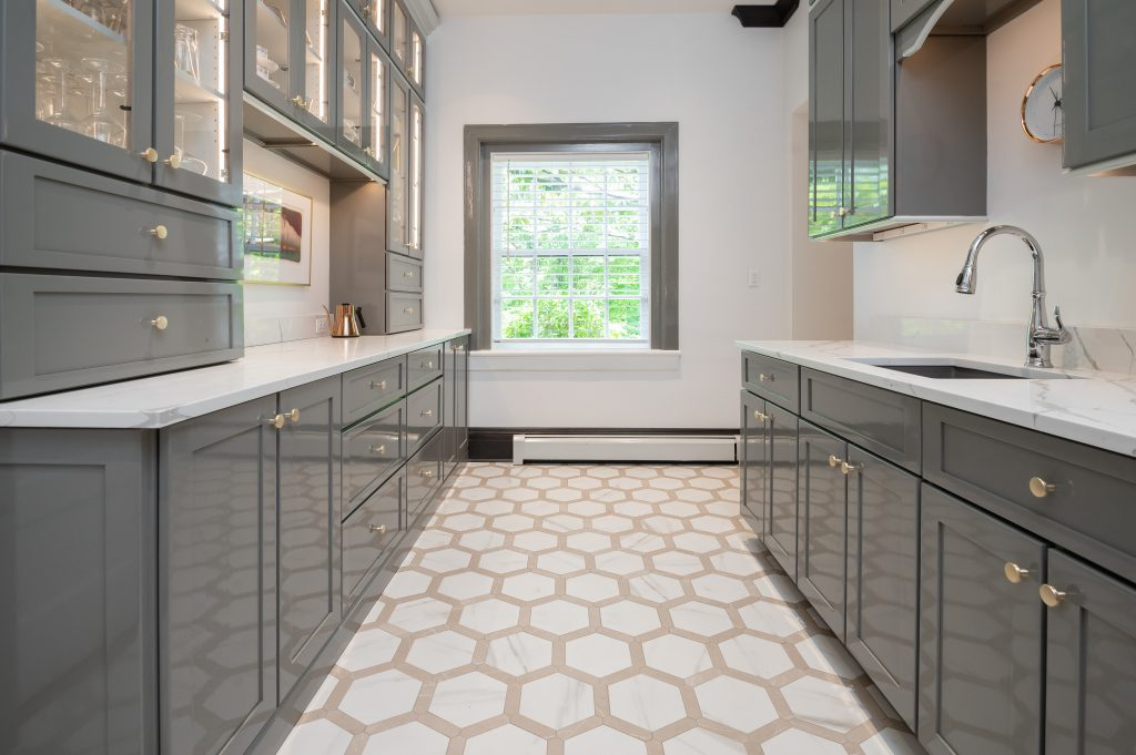 Transitional kitchenette with grey cabinetry, marble countertops, and hexagonal tile flooring