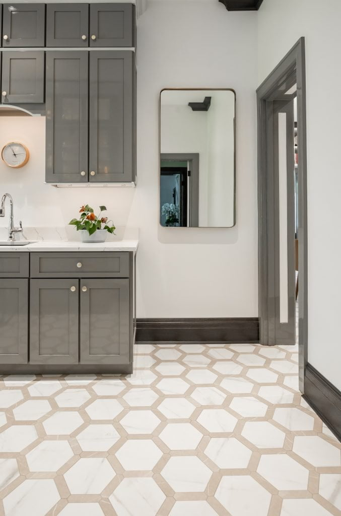 View of doorway from kitchen using painted grey molding and continuous hexagonal tile flooring